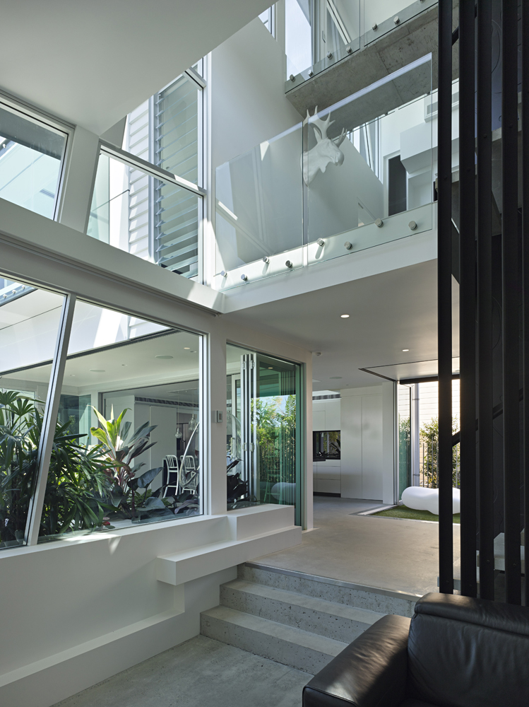 Coming up the main black metal and concrete staircase, we see the secluded garden at left through full height glass, as well as upper levels in multiple tiers wrapped in glass railing.