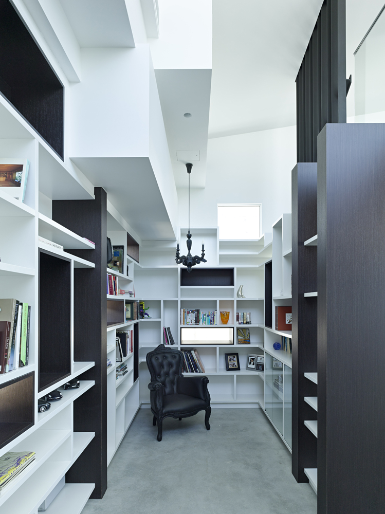 Cozy library space packs myriad shelving options on every wall, with dark stained wood punctuating the white decor. Ornate black accent chair stands at center.