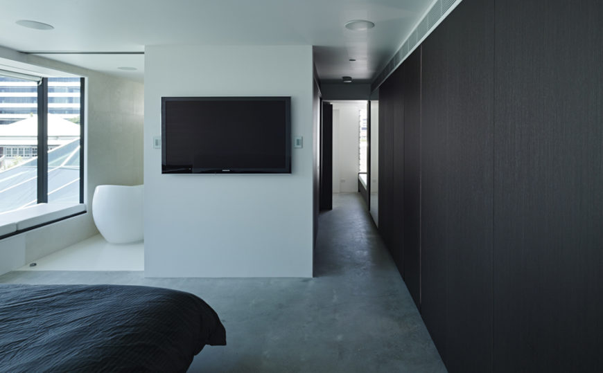 From the master bedroom suite, we see a lengthy hallway decked in black wood at right. Single wall mounted television breaks up the white walls, with bathroom entrance at left.