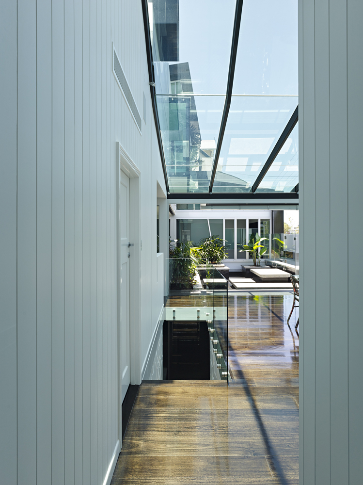 Looking down the length of the dining space over a wide expanse of dark natural hardwood flooring, we see the glass wrapped staircase and rooftop garden in distance.