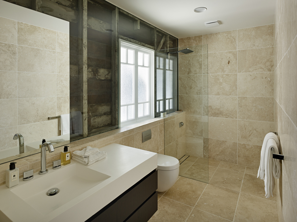 The open design shower is shielded via glass panel, continuing into wall, exposing original wood structure of the home.