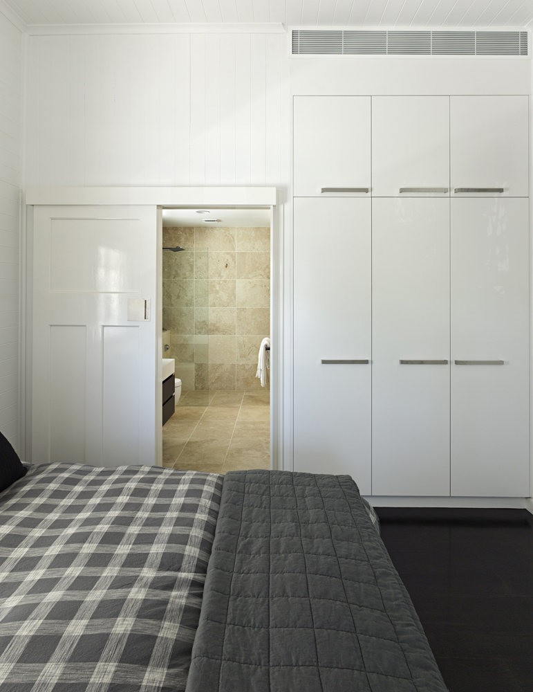 Bedroom features an array of minimalist white cabinetry blending into the wall, over black flooring, with sliding wood door to bathroom at center.