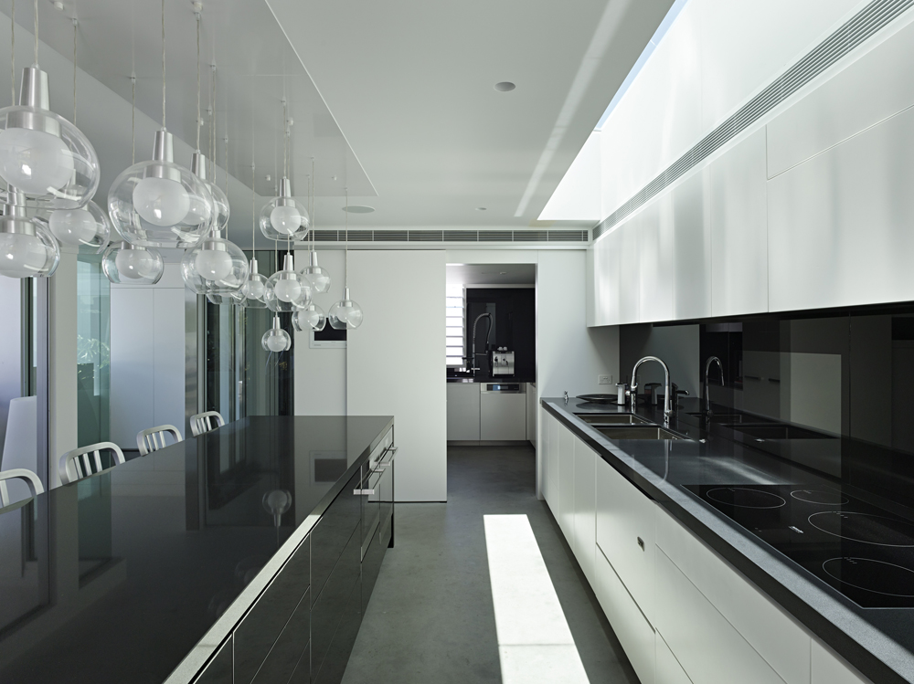 Taking another look at the kitchen, we see the black countertops with reflective backsplash at right, as well as partially hidden utility space in the distance, behind sliding white panel by Base Architecture.