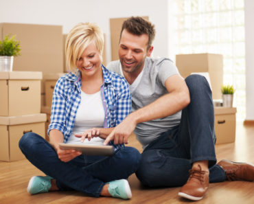 Couple researching furniture online in an empty house
