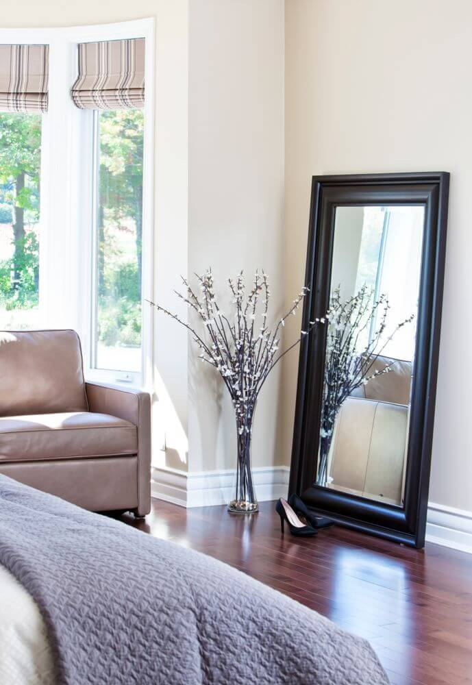 Looking over the bed, we see a large black-framed mirror leaning against the wall, next to window cove with brown leather armchair.