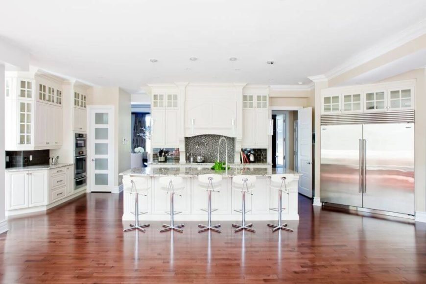 Kitchen is grand central in the home, with an array of white wood cabinetry circling steel appliances and a large island with marble countertop. Doorways at rear lead to private areas of the home.
