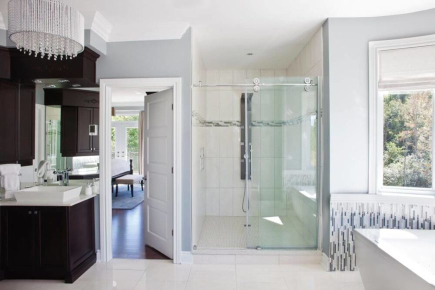 Wide view of the master bath shows large shower area and dark wood cabinetry flanking bedroom access door.