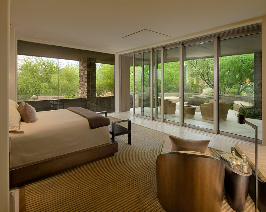 Master bedroom opens via sliding glass panels completely to the covered patio space. Floor to ceiling windows at left, with custom made carved wood chaise style chairs at right.