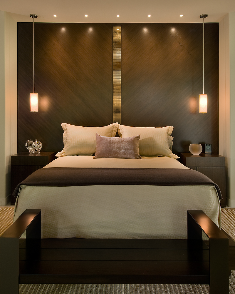 Master bed features a dark walnut headboard wall bisected by glass tile and matched with flanking bedside tables.