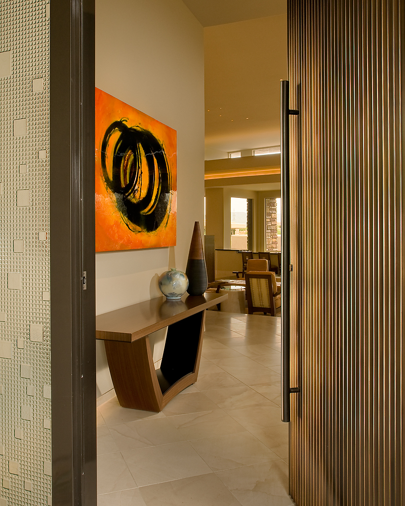 Entry door in fabricated metal, framed with a custom crafted glass panel at left. Floor tiles in Crema Europa limestone hold the custom natural wood tone entry table below a Quim Bove painting.