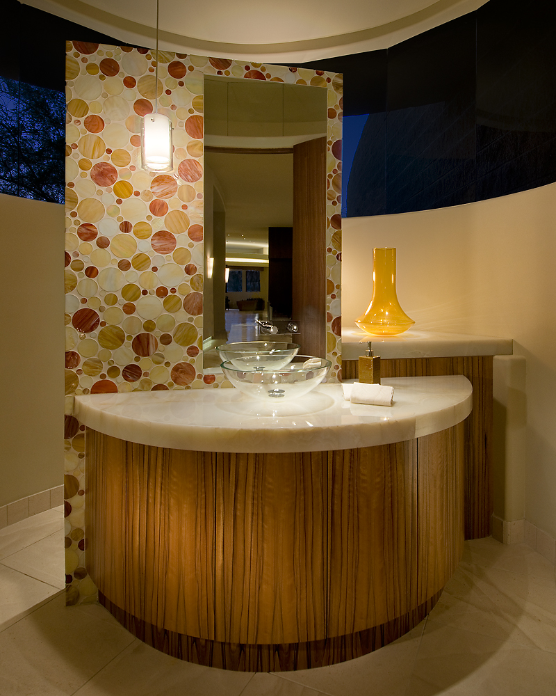 Powder room stands its split-circle, marble topped vanity around this striking glass mosaic clad wall holding the mirror. The wall obscures the plumbing facilities, adding bold detail.