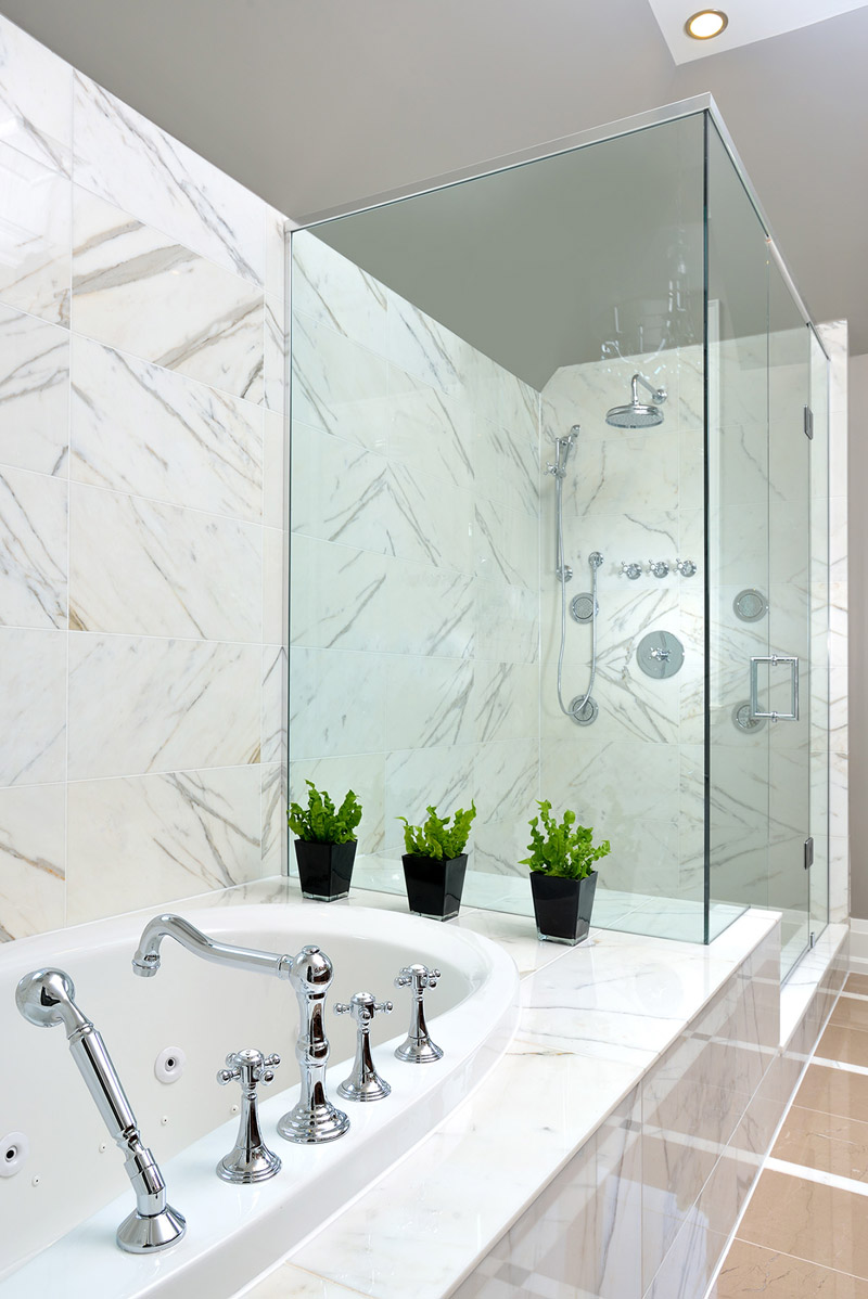 Large jacuzzi bath wrapped in marble, extending into the adjoining glass shower space.