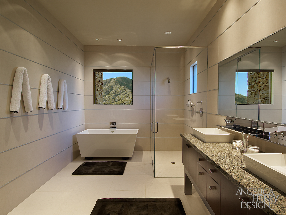 Guest bathroom features an all glass shower, angular pedestal tub, and cream colored tile throughout, with aluminum strips adding detail to the walls.