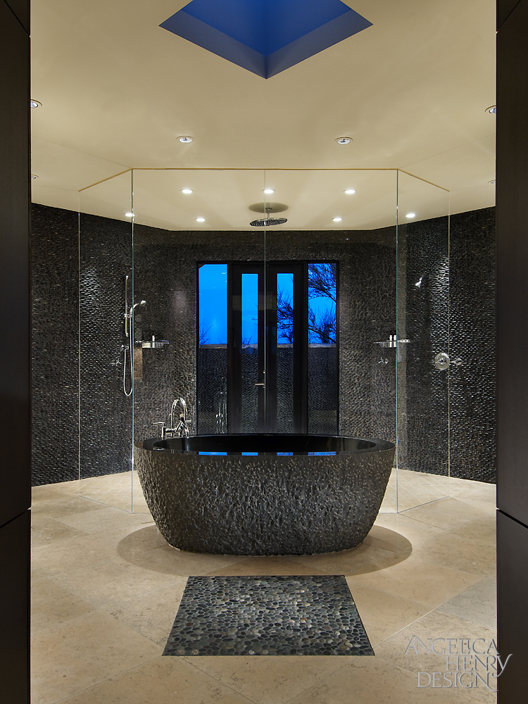 Master bath features this carved granite pedestal tub at center, with a massive, all-glass shower backdrop.