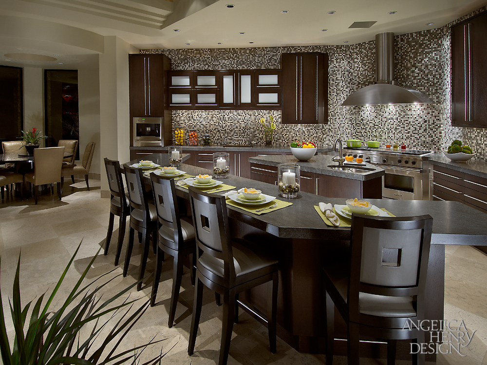 Kitchen features charcoal granite countertops and a pair of islands in dark stained oak. Smaller cooking island is surrounded by large dining island with rich wood bar stools eating.
