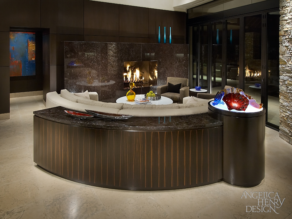 Curved sofa is backed by this marble topped, curved table with unique cylinder detail lit from within. Fireplace is surrounded by glossy marble slabs.