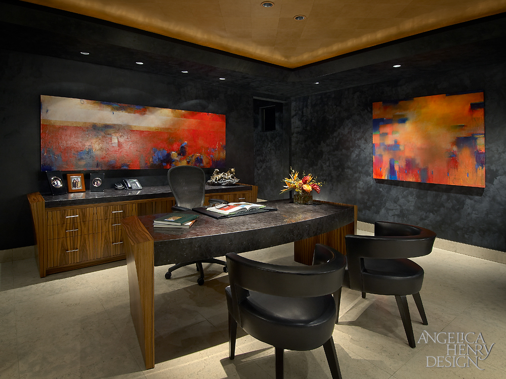 Dark toned office features granite topped desk and dresser in rich wood, with matching near-black walls holding bold colored paintings.