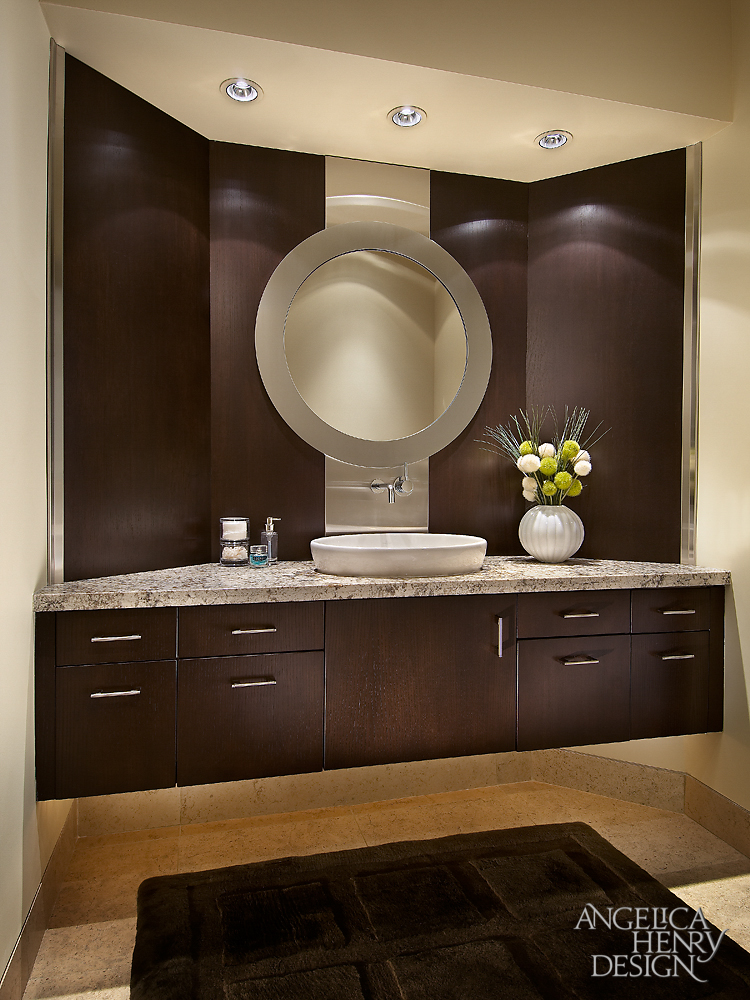 Master bath features this vanity in dark wood paneling, with circular mirror and stainless steel strip at center behind vessel sink.