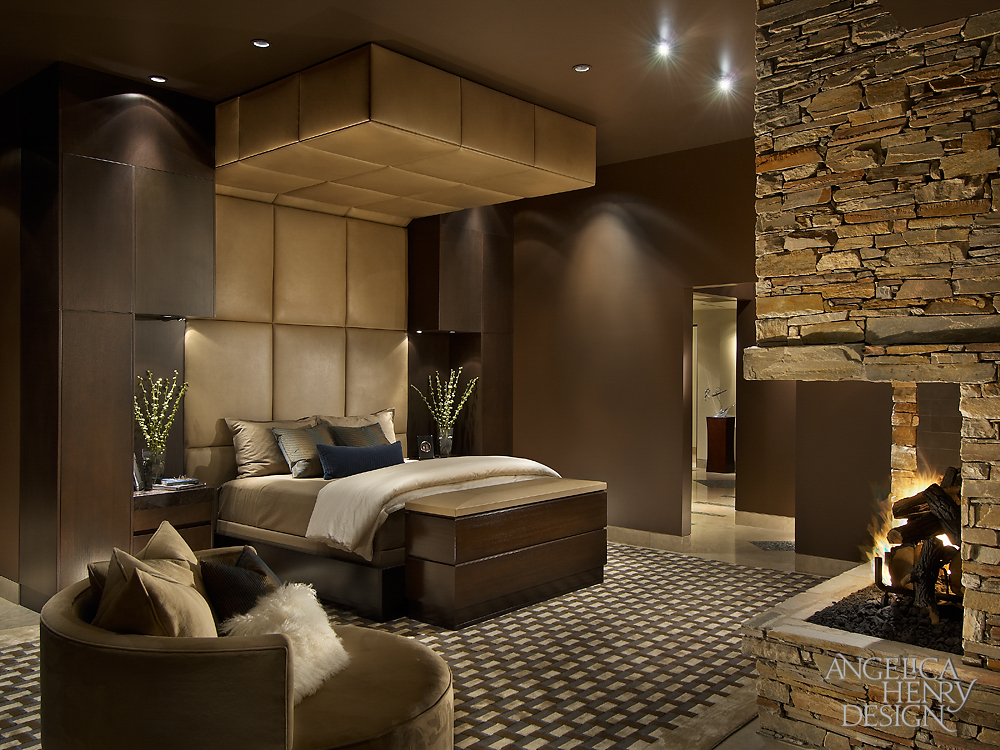 Master bedroom features a bed surrounded by an immense upholstered headboard and soffit, with a custom television lift at the foot. Stone corner fireplace stands across patterned rug, with custom circular armchair in corner.