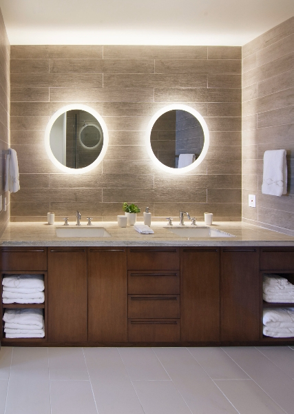 Bathroom contrasts natural wood cabinetry with light grey tile flooring and marble countertops, with dual vanity holding a pair of back-lit circular mirrors.