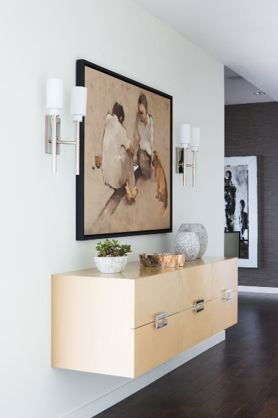 This floating cabinetry design is one of several slick, modern touches throughout the home. Natural wood material meets minimalist, modern design below a painting flanked by silver wall sconces.