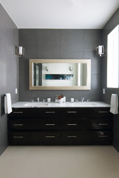 Second bathroom features black wood cabinetry contrasting with white marble countertop beneath a natural wood framed mirror. Walls are slate grey over the same light tile flooring.