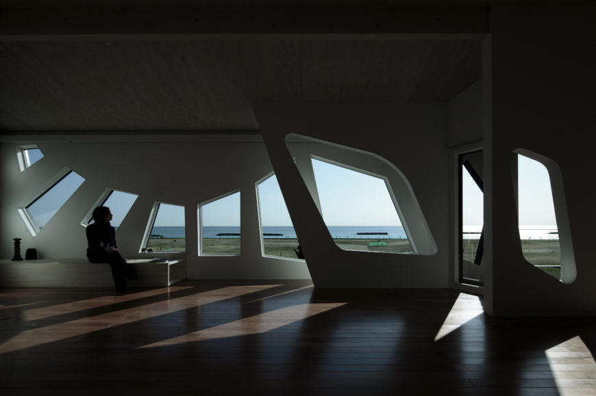 The angular windows are reflected in softer-edged cutouts within the interior walls. At left sits a small natural wood sitting space for gazing toward the ocean.