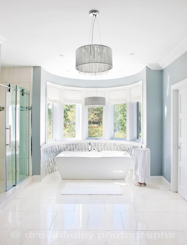 Master bath is awash in pristine white tile, with pedestal tub standing in curved window area next to sliding glass door shower.