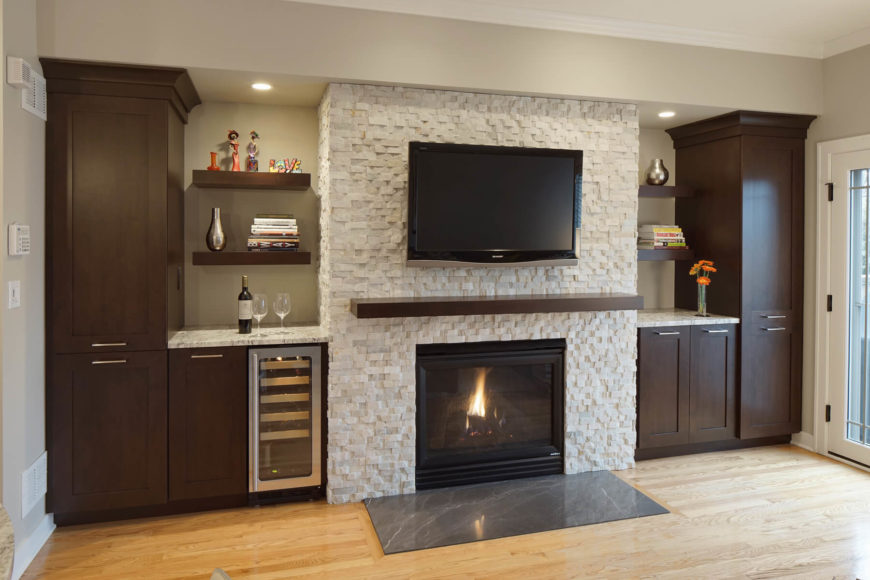 Sharp contrast defines this living room, with dark wood cabinetry flanking a white textured brick fireplace surround, over light natural hardwood flooring. The fireplace stands before a pad of dark marble, while the cabinetry features a built-in wine cooler and marble countertops beneath floating wood shelves.