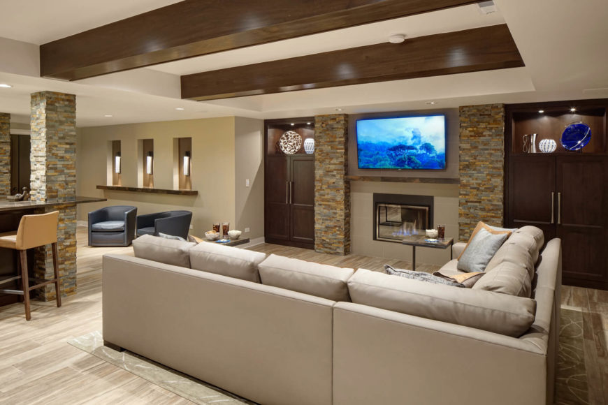Thoroughly modern family room joins an open space with the kitchen hinted at left, standing light hardwood flooring and a series of stone brick pillars beneath a white ceiling with exposed polished wood beams. Sharply defined L-shaped sectional commands the center, while rich wood cabinetry flanks a fireplace and television area.