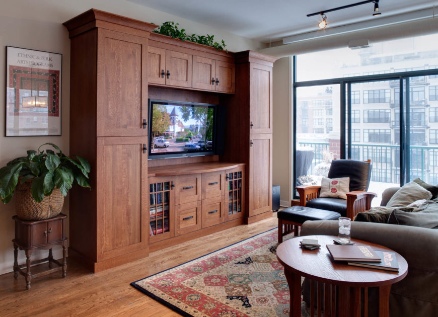 This high rise family room expresses a natural setting with hardwood flooring and warm toned, full height wood cabinetry housing the television at center. Wood framed, leather cushion armchair stands before floor to ceiling sliding glass, allowing for expansive city views and balcony access.