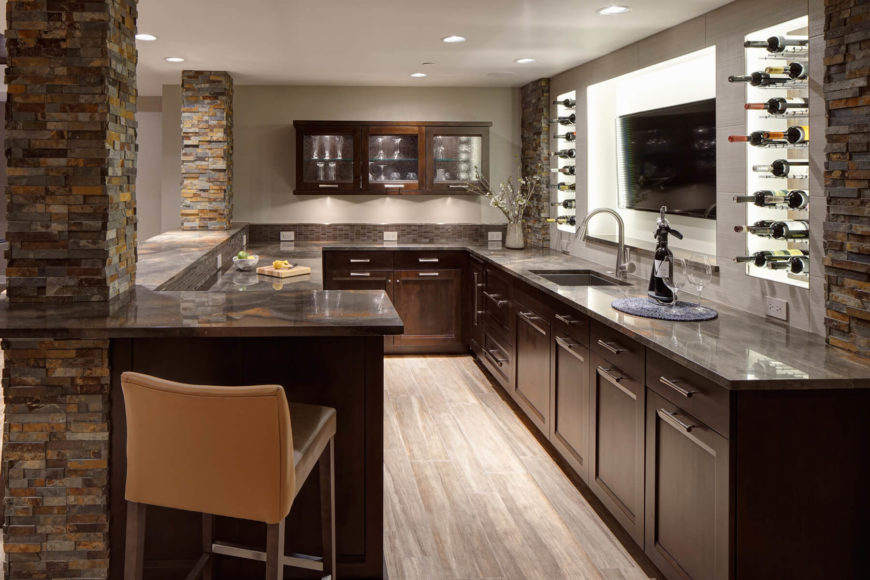 The Bar Cabinetry Features Stainless Hardware Beneath Quartzite  Countertops, While Sink Is Backed By A