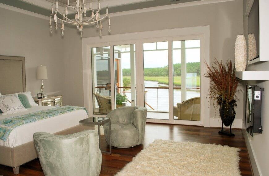 Mint chairs and blanket accent this predominately white and cream master  bedroom. A plush white