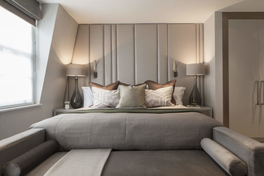 The master bedroom continues the unifying neutral, grey toned theme. Backless sofa stands at the foot of the bed, making for a continuous relaxation piece.