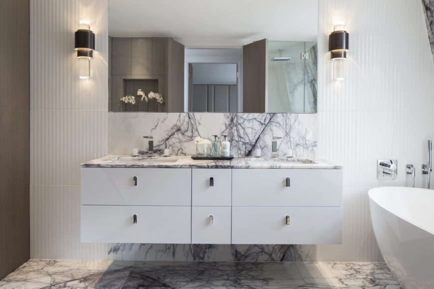 Master bath holds a striking use of textural marble, with flooring reaching up through the floating white vanity to encompass a backsplash space. Modernist cylindrical sconces flank the frameless mirror on a rippled texture wall.