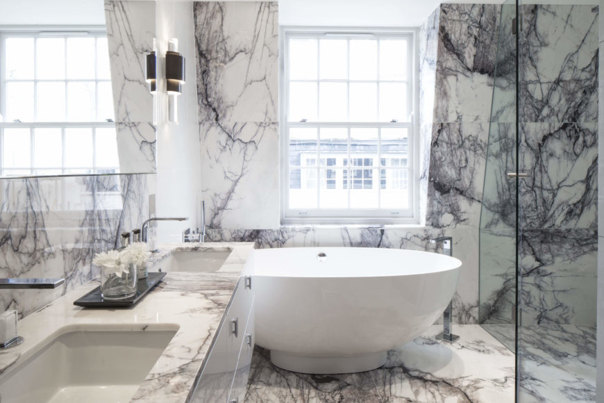 Exquisitely veined marble fills the bathroom, continuing through the glass enclosure shower and wrapping the bowl shaped pedestal tub beneath a large window.