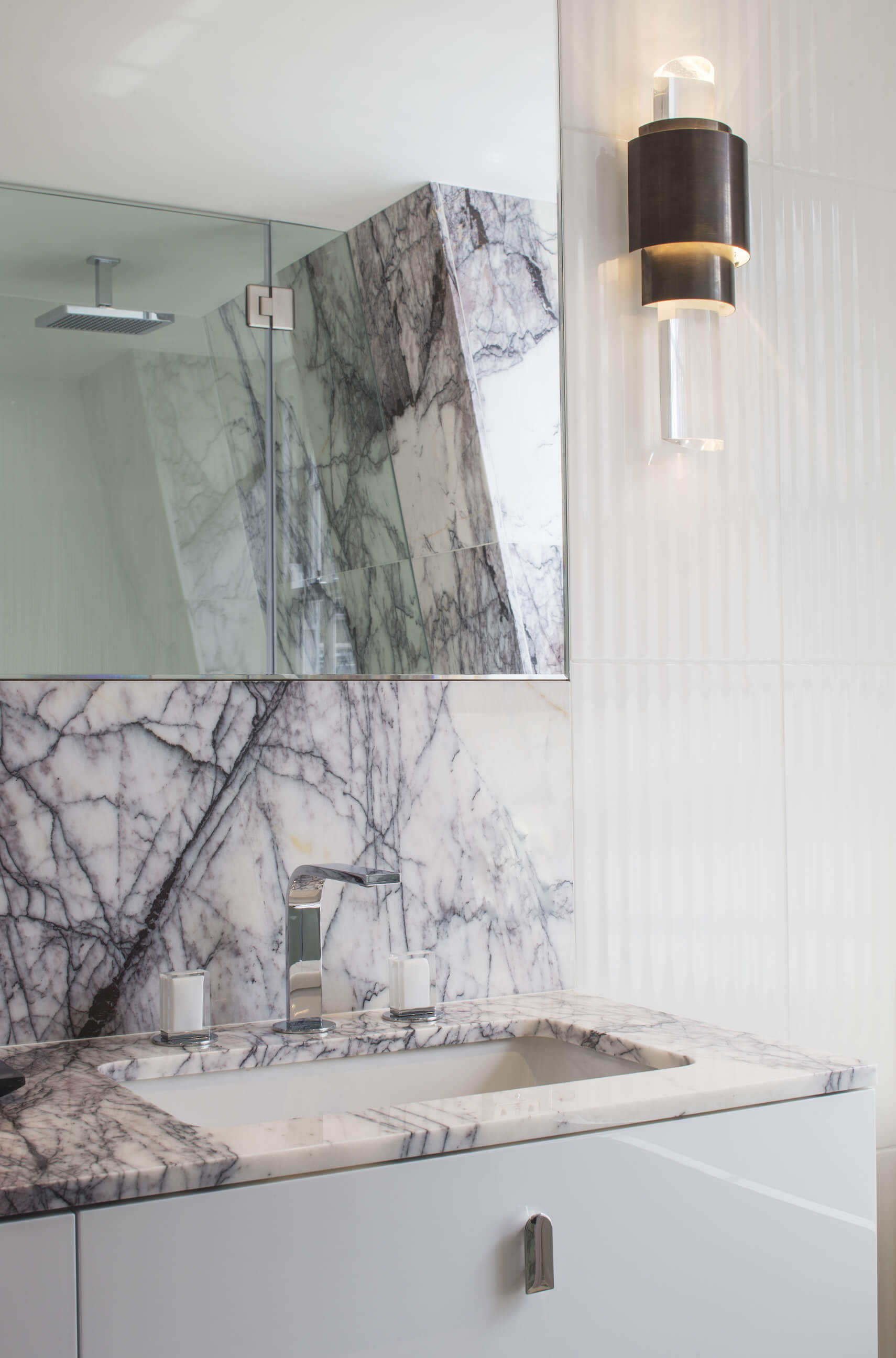 The vanity pops with detail, including this novel curved, flat faucet design with glass handles. The slanted wall embracing the glass shower can be seen in reflection.