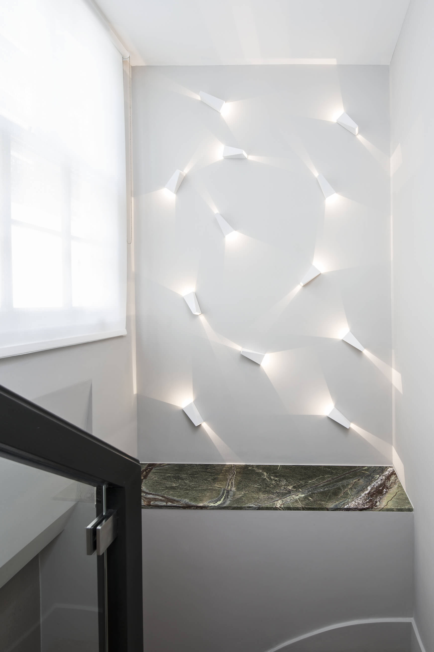 The main staircase wall holds this truly unique feature: angled light housings arrayed like a series of roving flashlights above a deep marble surface.