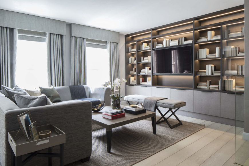 Casual family room with wall of bookshelves framing TV by Roselind Wilson Design