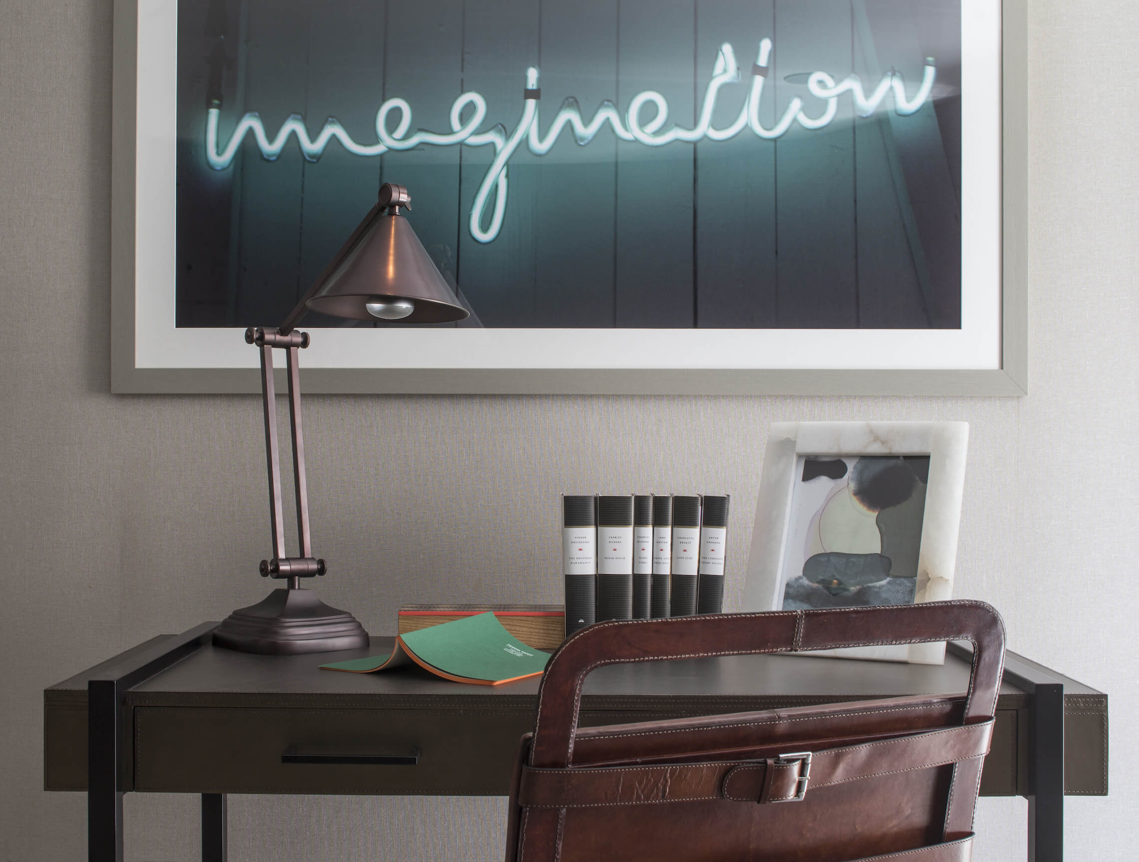 "Above the sleekly minimalist desk hangs a neon ""imagination"" art piece, adding a splash of glowing color to the space."