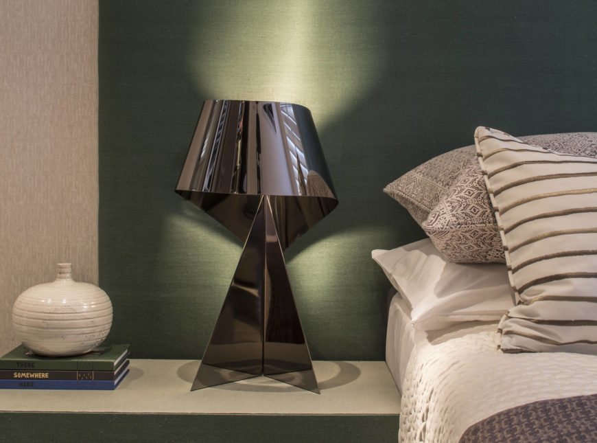 The bedside dresser matches the wall tones perfectly, holding this ribbon styled metal lamp.