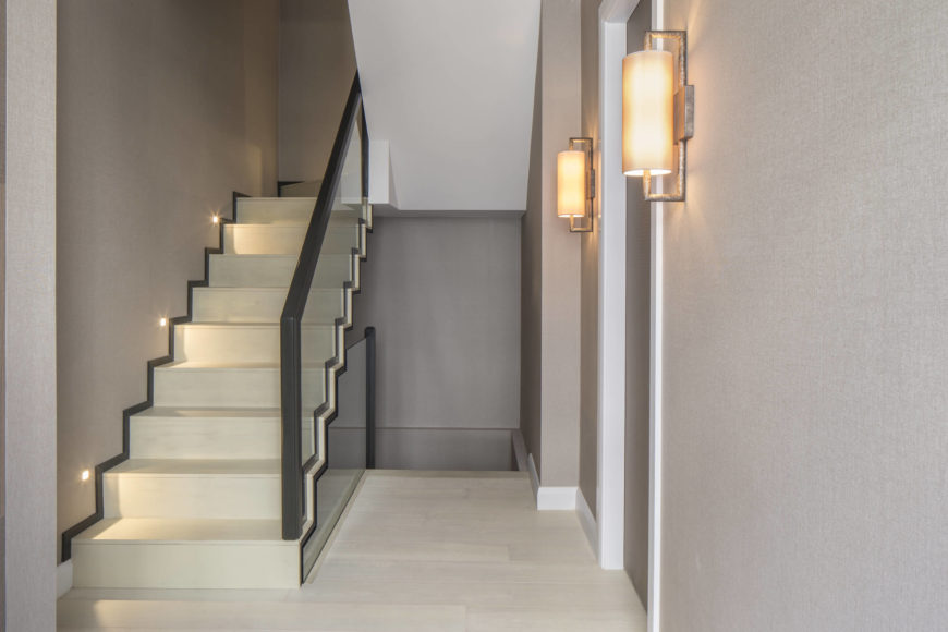 The staircase itself in light bone color is framed in dark toned railings on glass. More modernist sconces are seen on this landing, flanking a doorway.