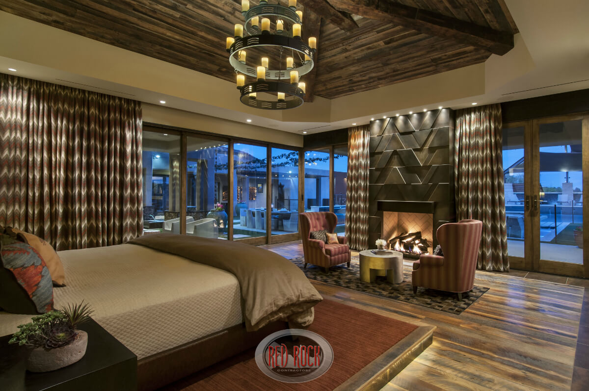 Bedroom sitting area with fireplace - Rustic Chandelier Hangs Above A Bed On A Raised Platform Of Natural Wood Matching Armchairs