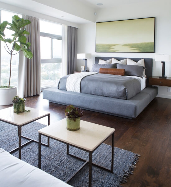 Slate-blue bedding, bed platform and rug are paired with rich dark hardwood  floors