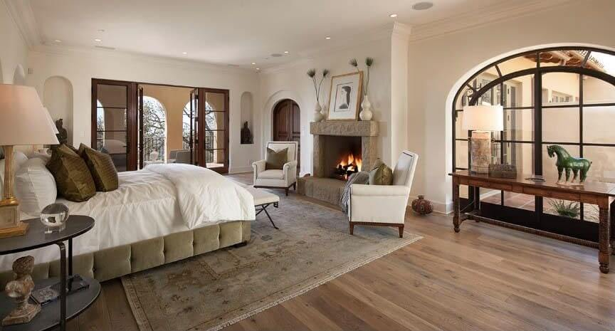 Light hardwood floors are covered by a beige patterned rug. An arched  window provides a