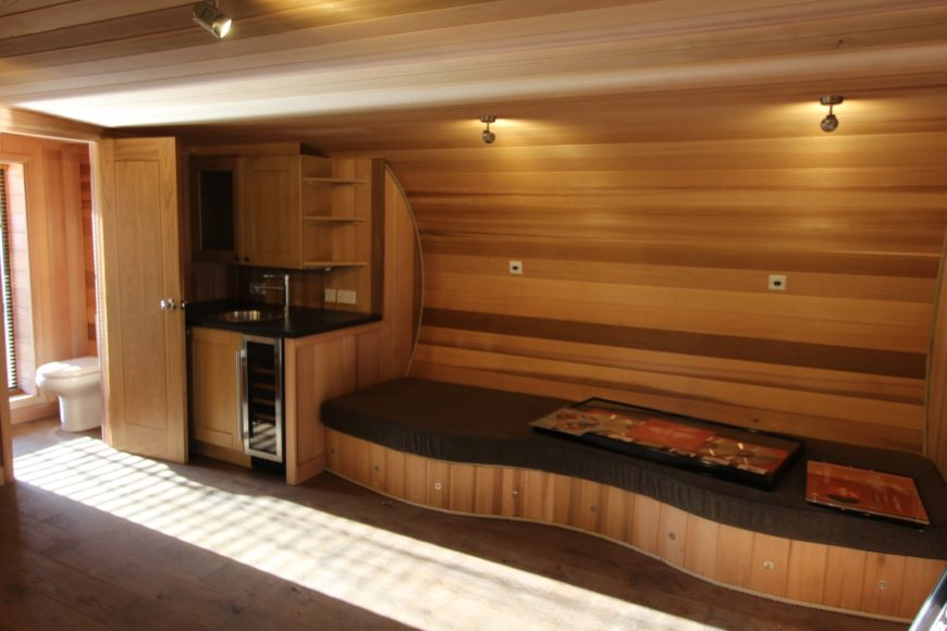 In addition to the mixing desk and mobile sound booth, the ecoPerch studio is conducive to relaxation, replete with this large built-in sofa and small kitchenette, including wine cooler. Canister lighting throughout provides focused illumination.