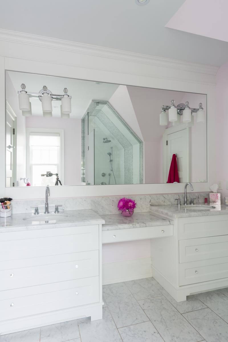 Bright master bath features marble countertops matching the tile flooring, with white dual vanity standing beneath an immense mirror.