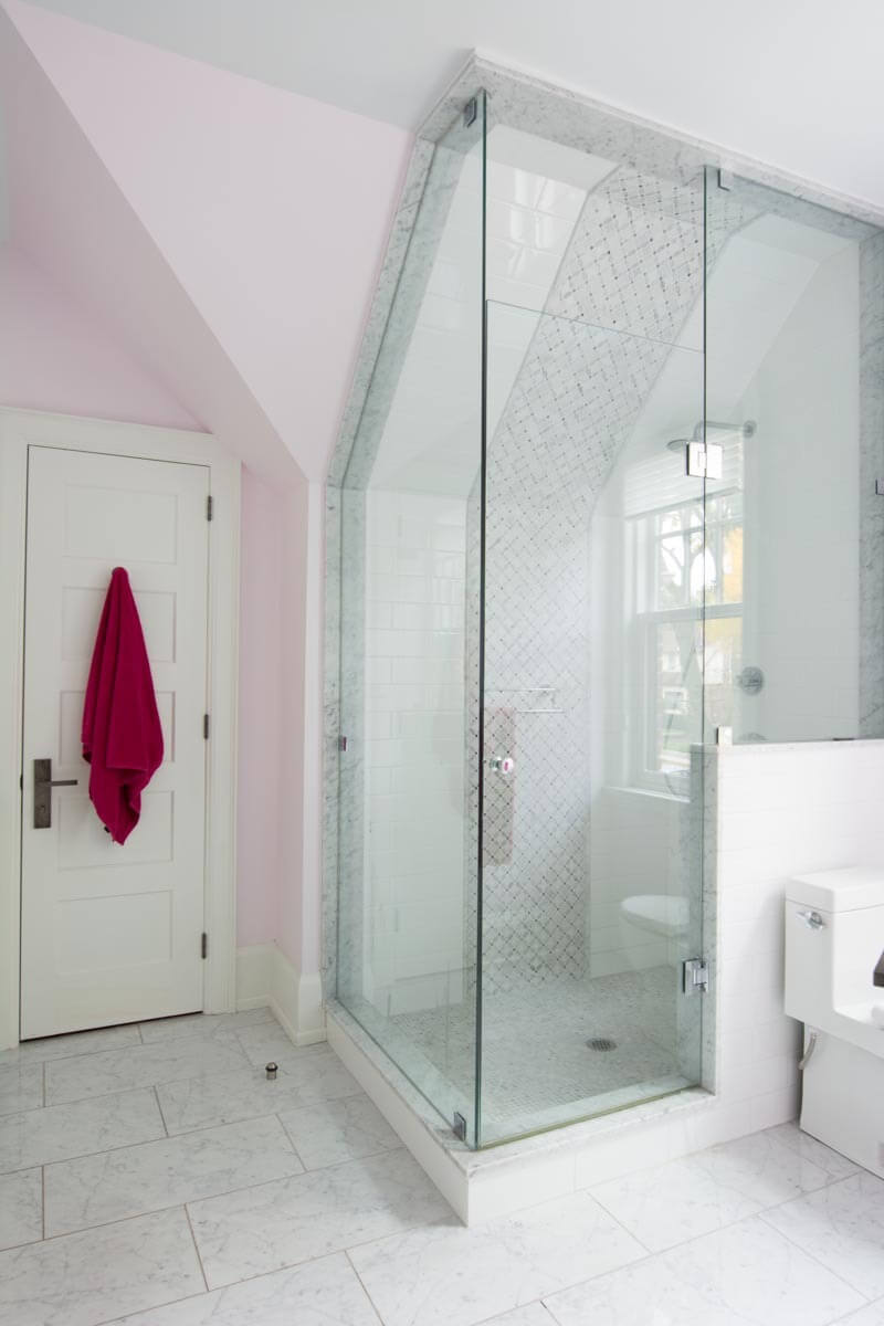 The bathroom features light pink wall painting, adding a splash of color to an otherwise white space. Corner glass enclosure shower sits below slanted ceiling, with patterned tile wall reaching all the way up.