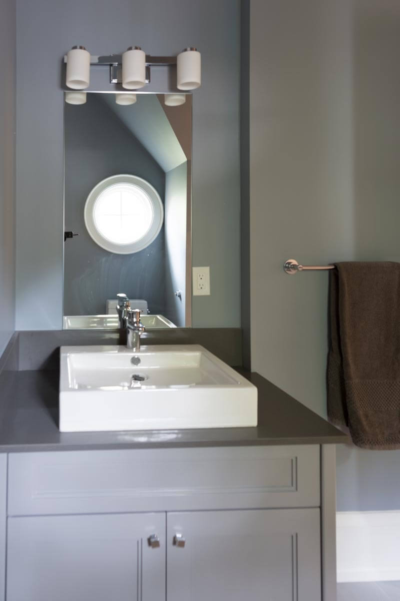 Second bathroom features this cozy vanity with square white porcelain vessel sink.
