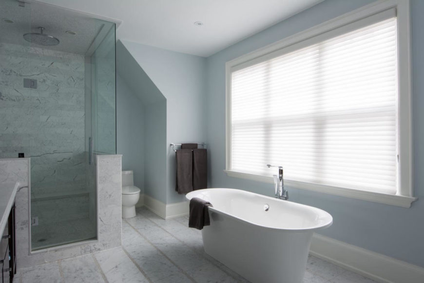 Bathroom also features a large white pedestal tub at center, beneath an immense window affording views and natural light. Class enclosed shower at left features rainfall shower head.